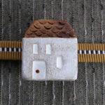 台形屋根の家の帯留 正面