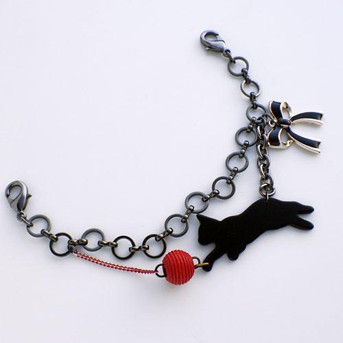 黒猫がじゃれる羽織紐 斜めから